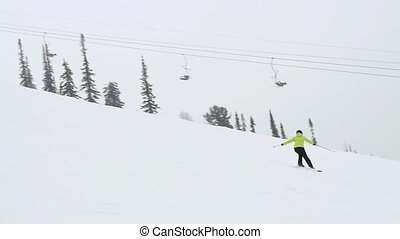 Female skier on downhill race with mountain view in...
