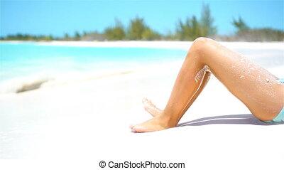 Female slim tanned legs on a white tropical beach. SLOW...