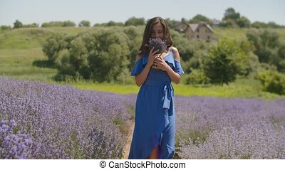 Female smelling fresh fragrant lavender blossoms - Charming...