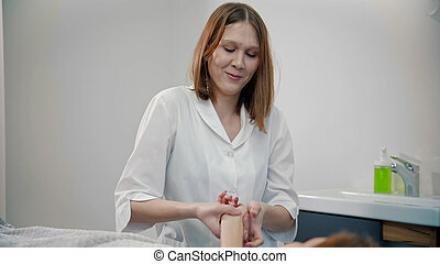 Female smiling massage therapist massaging hands of her client