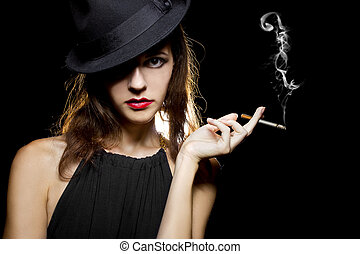 Female Smoker - young female in stylish hat smoking a lit...
