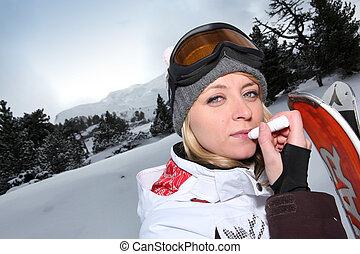 Female snowboarder applying lip balm