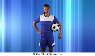 Female soccer player against abstract blue background