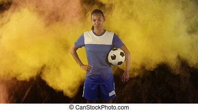 Female soccer player against smoke explosion in background