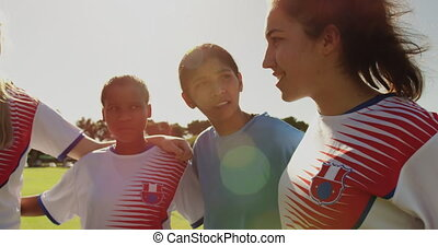 Female soccer player encouraging her team while standing arm...