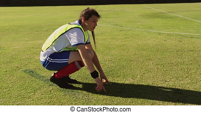 Side view of young Caucasian female soccer player explaining strategy while sitting in squat position on soccer field 4k
