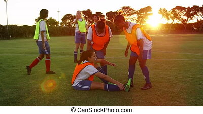 Female soccer player helping teammate to stand on soccer ...