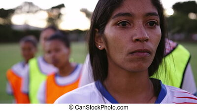 Female soccer player standing in front of her diverse female...