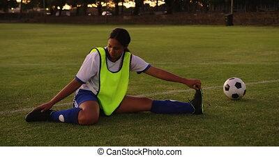 Female soccer player stretching her legs on soccer field. 4k...