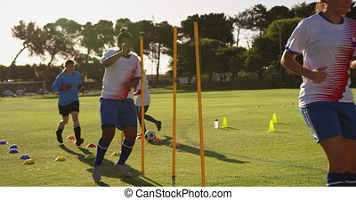 Female soccer players doing exercises with equipment. 4k - ...