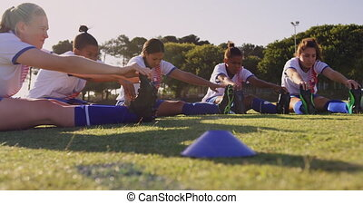 Female soccer players sitting on the ground and touching ...