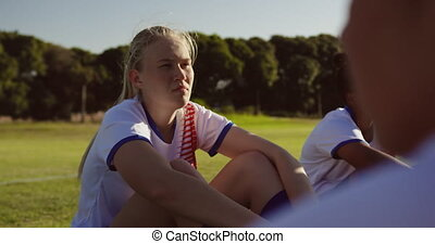 Female soccer players sitting on the ground on soccer field...