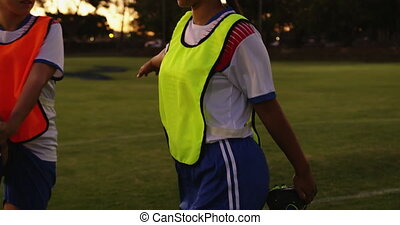 Female soccer players stretching their legs on soccer field...