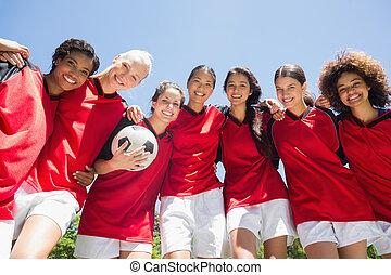 Female soccer team against clear blue sky - Portrait of...