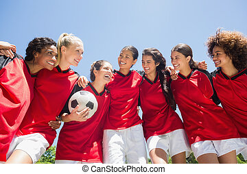 Happy female soccer team with ball against clear blue sky