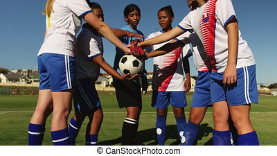 Female soccer team clasping hands together on soccer field. ...