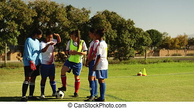 Front view of diverse female soccer team discussing tactics on soccer field on sunny day. 4k