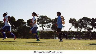 Female soccer team running lapse on soccer field. 4k - Side ...