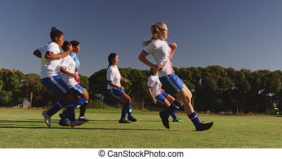 Side view of diverse female soccer team running while Caucasian team captain gives instructions on soccer field on sunny day. 4k