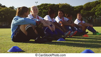 Female soccer team sitting on the ground while talking on ...