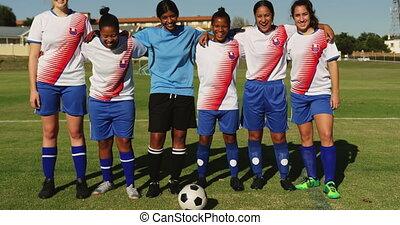 Female soccer team standing arm to arm on soccer field. 4k...