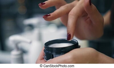 Female softly takes beauty cream with fingers from black...