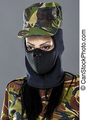Female soldier in camouflage outfit and mask