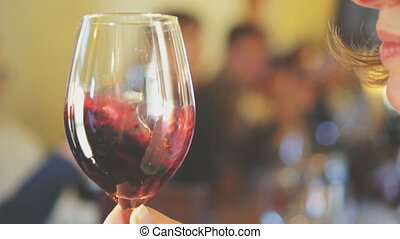 Female sommelier sniffs glass of wine before drinking.