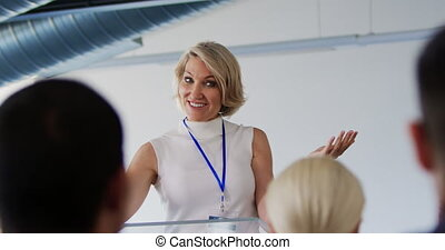 Female speaker addressing the audience at a business ...