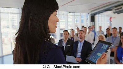 Female speaker addressing the audience at a business seminar...