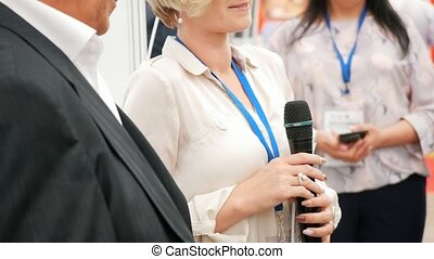 Female speaker at business conference speaks into the microphone