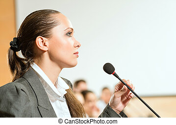 female speaker looks into the room and said into the...