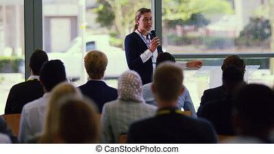 Female speaker speaks in a business seminar at modern office...
