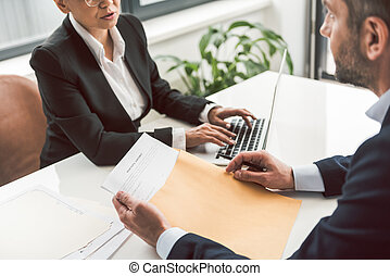 Female speaking with man at desk