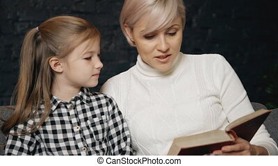Female spending free time and reading book with her child -...