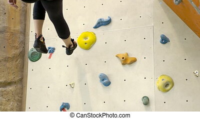 Female sports figure goes back down on the climbing wall. On...