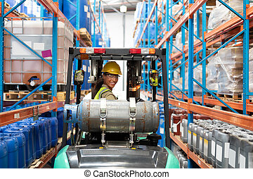 Female staff driving forklift in warehouse