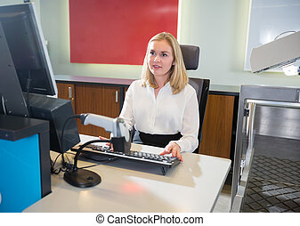 Female Staff Using Computer At Airport Check-in