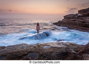 Female standing on shipwreck rock with ocean awash flowing over it