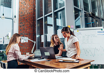 Female start-up team having a conversation about new project sitting at desk using computers in creative studio