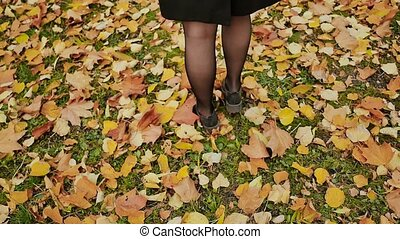 Female steps along the colorful autumn foliage of the city park. Walk in the autumn.
