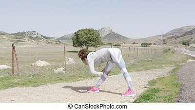 Female stretching during workout on nature