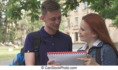 Female student asks her classmate about something in notebook on campus