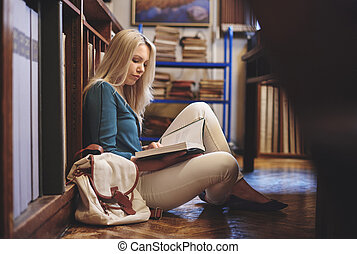 Female student at library reading book
