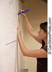 Female student graphing the equation of a line