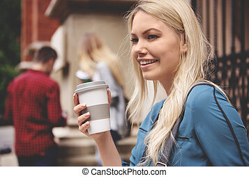 Female student holding hot coffee