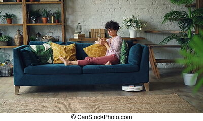 Female student is using smartphone relaxing on sofa while...