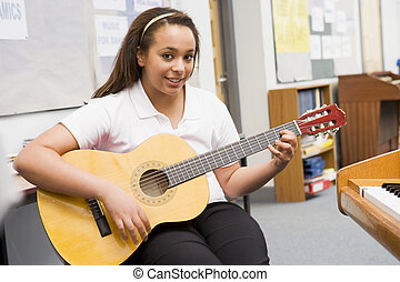 Female student learning guitar in classroom