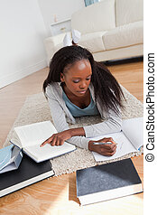 Female student lying on carpet doing her homework