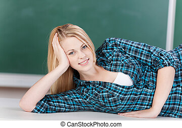Female Student Lying On Desk In Classroom